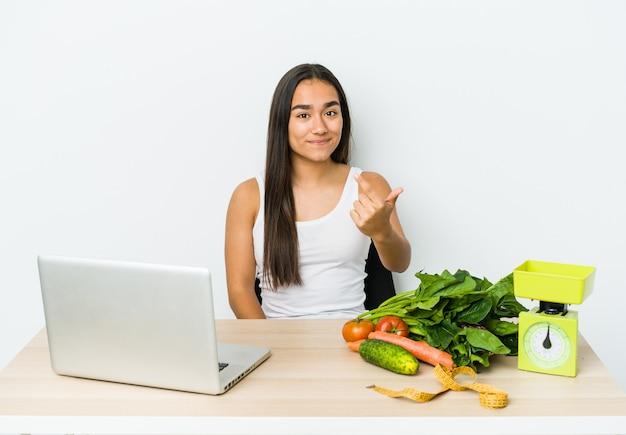 Giovane donna asiatica dietista isolata su sfondo bianco che punta il dito contro di te come se invitando si avvicinano.