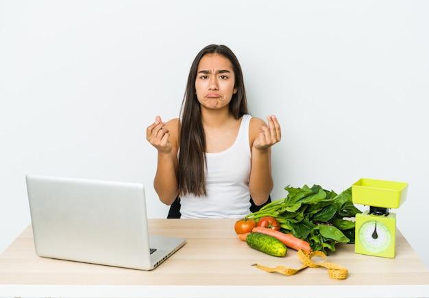 Giovane donna asiatica dietista isolata su bianco che mostra che non ha soldi.