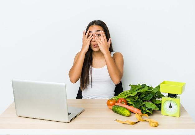 La giovane donna asiatica dietista isolata sul muro bianco lampeggia attraverso le dita spaventata e nervosa.