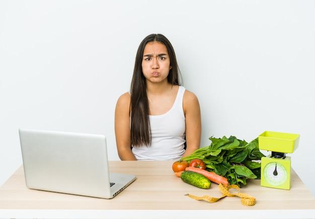 La giovane donna asiatica del dietista isolata sulla parete bianca soffia sulle guance, ha un'espressione stanca. concetto di espressione facciale.