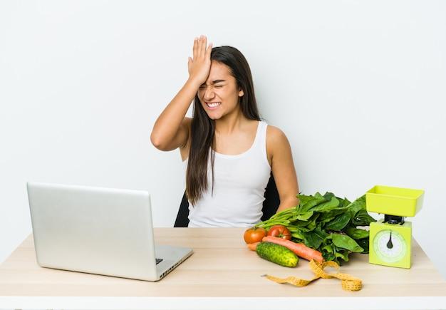 Giovane donna asiatica dietista isolata sul muro bianco dimenticando qualcosa, schiaffi sulla fronte con il palmo e chiudendo gli occhi