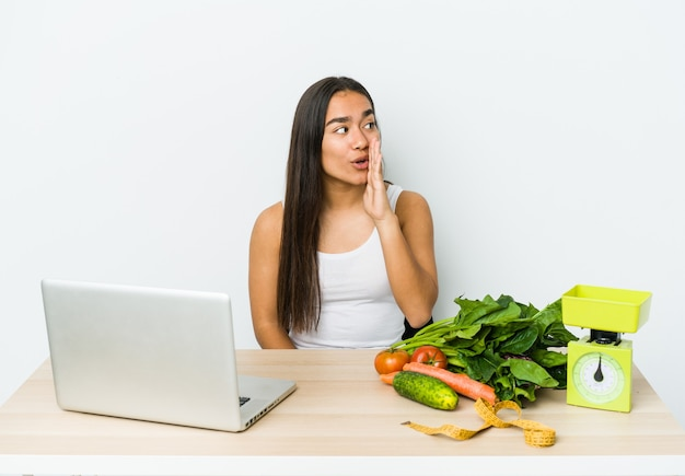 La giovane donna asiatica del dietologo isolata sulla parete bianca sta dicendo una notizia di frenata calda segreta e sta guardando da parte,