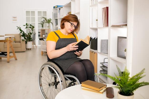 Giovane donna disabile in abbigliamento casual e occhiali da vista che si siede sulla sedia a rotelle dallo scaffale e legge il libro mentre riceve l'istruzione domestica