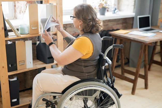 Giovane impiegato femminile disabile in abbigliamento casual che guarda attraverso i documenti in una delle cartelle con documenti durante la ricerca di un esempio di contratto
