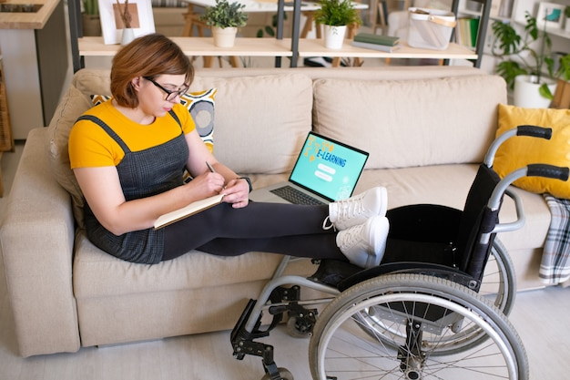 Giovane studentessa disabile in abbigliamento casual che si siede sul divano nel soggiorno davanti al computer portatile e prende appunti durante il seminario o la lezione online