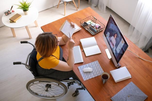 Giovani disabili insegnante femminile che consulta lo studente in linea e spiega le note nel quaderno mentre era seduto in sedia a rotelle dal computer