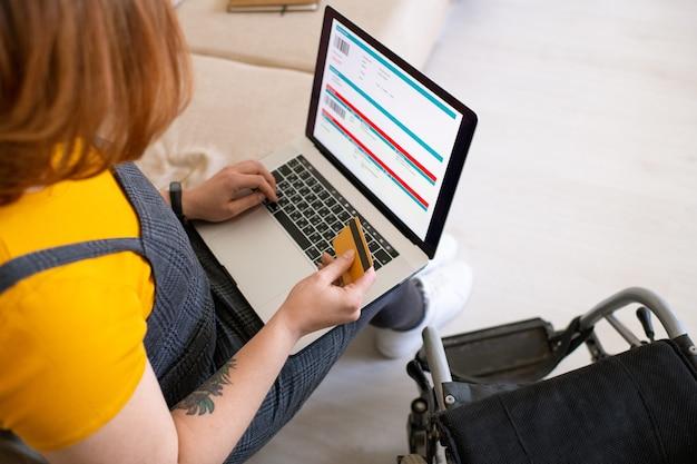 Giovane donna disabile con carta di credito sulla tastiera del laptop seduto sul divano mentre va a prenotare e pagare i biglietti aerei da casa