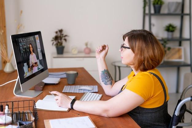 Giovane insegnante disabile o consulente educativo in sedia a rotelle seduto alla scrivania davanti al computer e parlando con studentessa di razza mista
