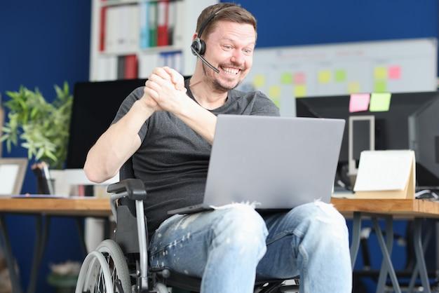 Giovane uomo disabile in cuffie che comunicano tramite laptop. concetto di incontri online