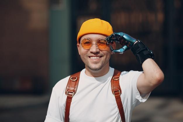 Il ritratto del giovane disabile ha messo gli occhiali gialli con la mano protesica artificiale