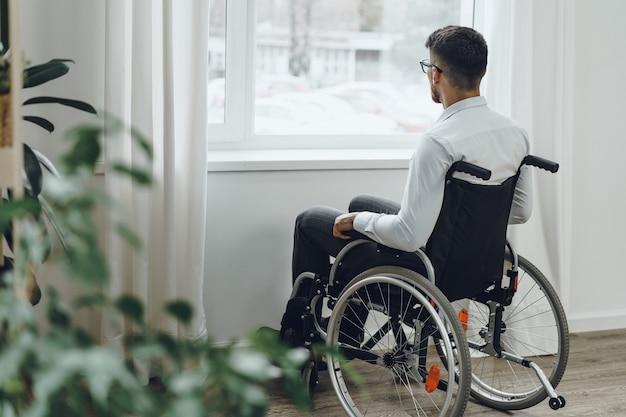 Giovane uomo disabile seduto su una sedia a rotelle vicino alla finestra di casa