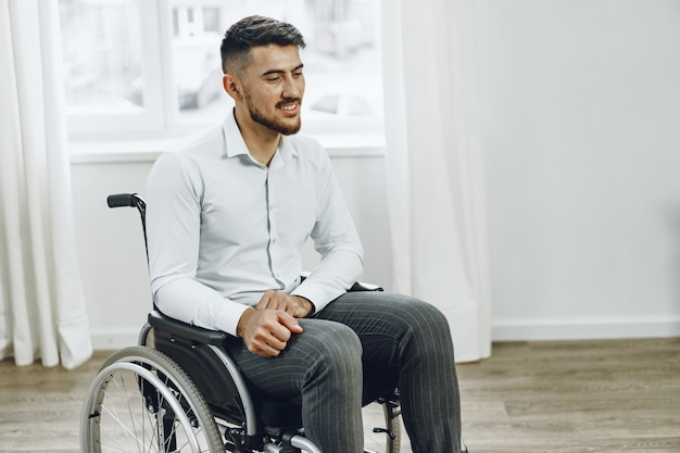Giovane uomo disabile seduto su una sedia a rotelle vicino alla finestra