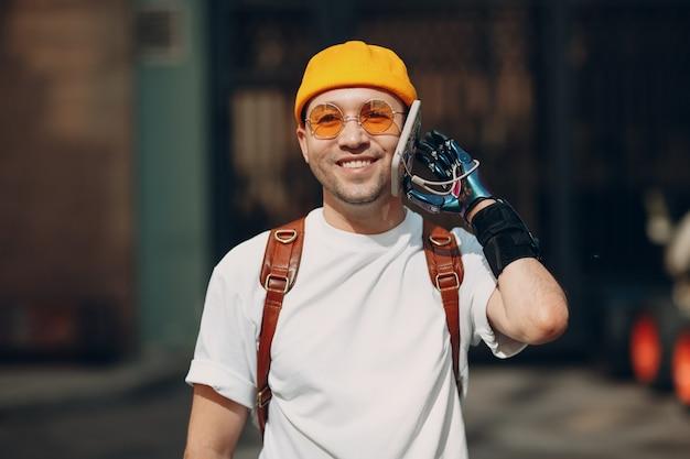 Giovane uomo disabile che utilizza il telefono cellulare con la mano protesica artificiale della cinghia della cintura in abiti casual