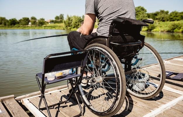 Giovane uomo disabile in una pesca in sedia a rotelle