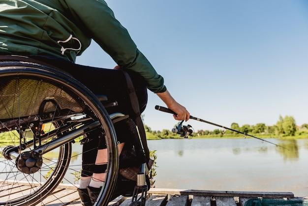 Giovane uomo disabile in una pesca in sedia a rotelle.