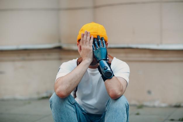 Il giovane uomo triste sconvolto disabile con la mano protesica artificiale chiude il viso seduto sul marciapiede della città...