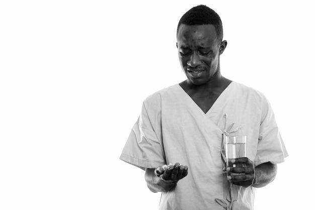 Paziente giovane uomo africano nero disgustato guardando compresse di vitamina e tenendo il bicchiere d'acqua