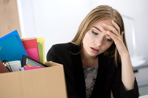 Giovane lavoratrice licenziata seduta vicino alla scatola di cartone con le sue cose in ufficio non sapendo cosa fare dopo. concetto di licenziamento.