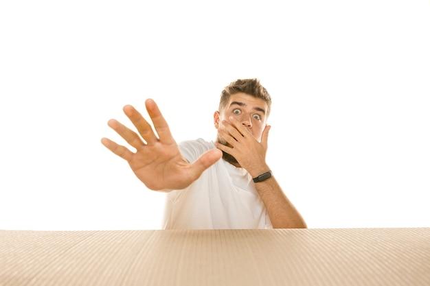 Giovane uomo deluso che apre il più grande pacchetto postale isolato su bianco. modello maschio scioccato sopra una scatola di cartone che guarda dentro.