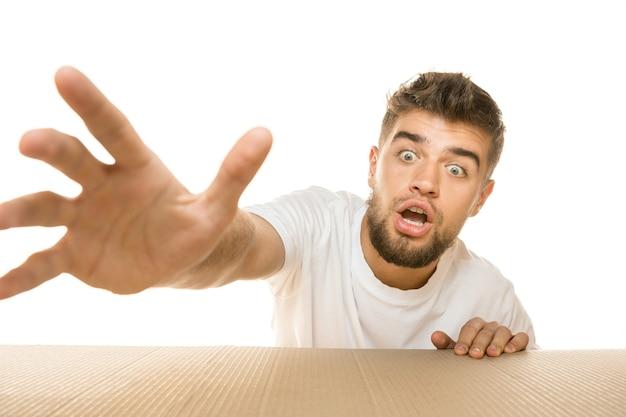 Giovane uomo deluso che apre il pacco postale più grande isolato sul muro bianco