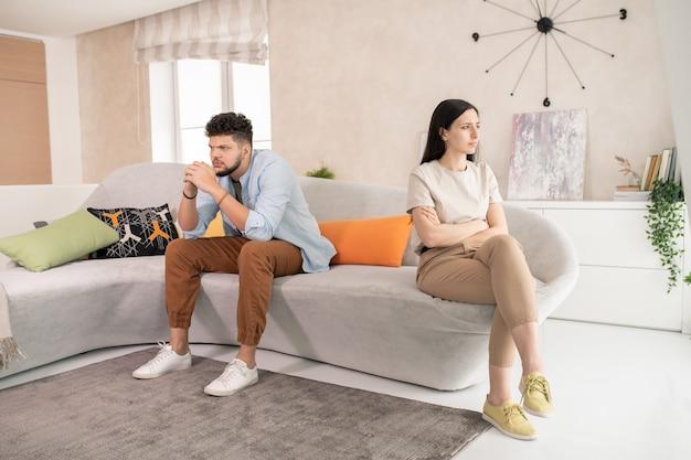Giovane donna bruna insoddisfatta che incrocia le braccia per il petto mentre è seduta sul divano in soggiorno contro il marito pensieroso o offeso
