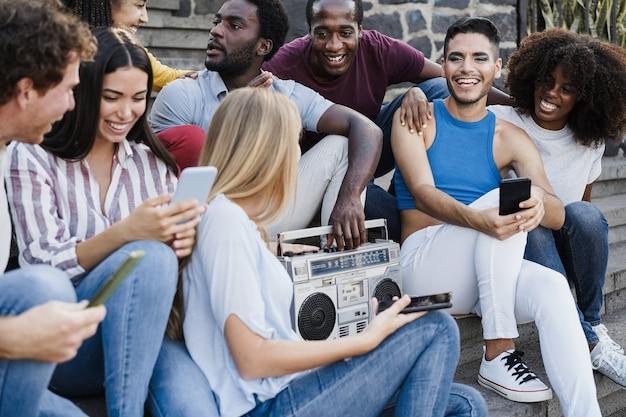Giovani persone diverse che ballano e ascoltano musica con stereo boombox all'aperto in città - focus principale sul volto dell'uomo transgender
