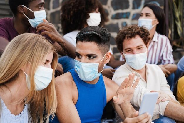 Giovani persone diverse che si divertono insieme indossando maschere di sicurezza all'aperto in città - focus sulla faccia della drag queen