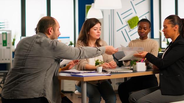 Giovane team diversificato di lavoratori che parlano, guardano documenti e analizzano i dati dei grafici seduti alla scrivania del posto di lavoro in una società di start up. team di colleghi professionisti che discutono del progetto di marketing.