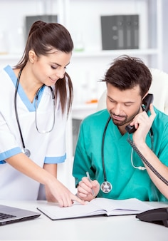 Giovane medico e il suo assistente in uno studio medico al lavoro.