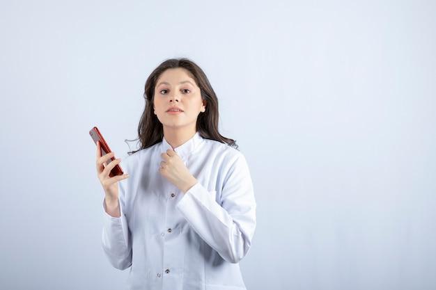 Giovane medico che tiene cellulare sul muro bianco.