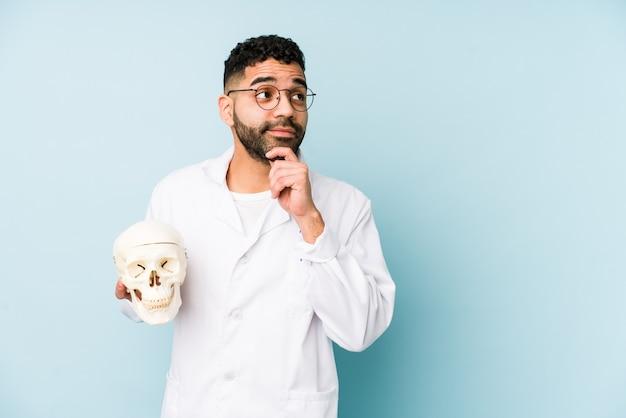 Uomo latino del giovane medico che tiene un cranio isolato che guarda lateralmente con espressione dubbiosa e scettica.