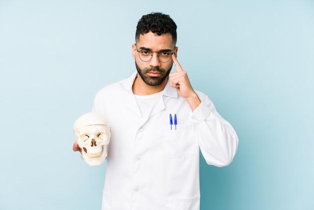 Giovane medico latino uomo che tiene un teschio isolato tempio puntato con il dito, pensando, concentrato su un compito.
