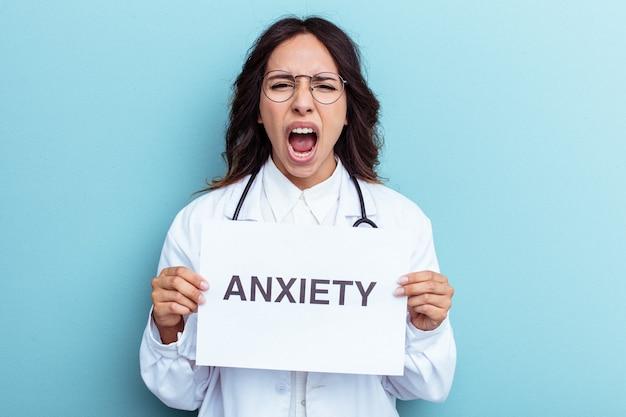 Giovane medico donna latina che tiene un cartello di ansia isolato su sfondo blu blue