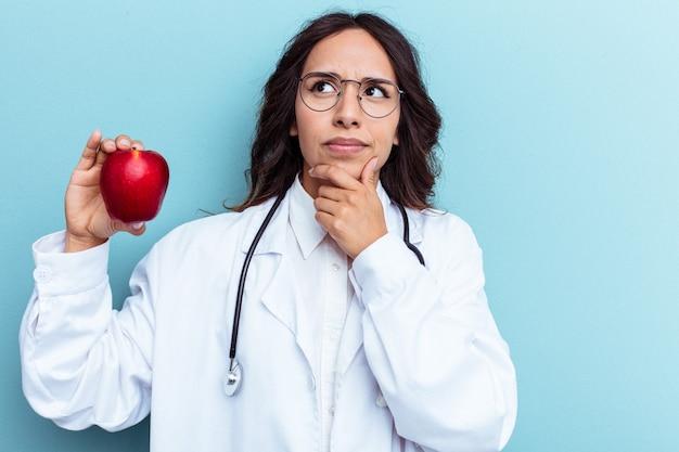Giovane medico donna latina che tiene una mela isolata su sfondo blu