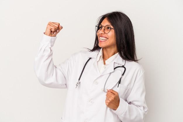 Giovane medico donna latina isolata su sfondo bianco alzando il pugno dopo una vittoria, concetto vincitore.