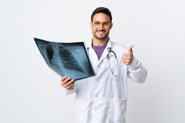 Uomo del giovane medico che tiene una radiografia isolata su fondo bianco che dà un pollice in alto gesto