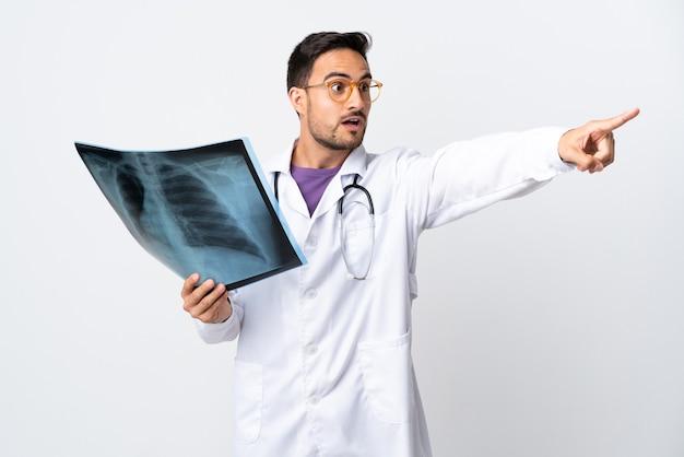 Uomo del giovane medico che tiene una radiografia isolata su fondo bianco che indica via