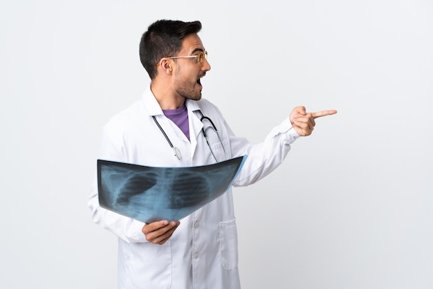 Uomo del giovane medico che tiene una radiografia isolata su priorità bassa bianca che indica il dito a lato