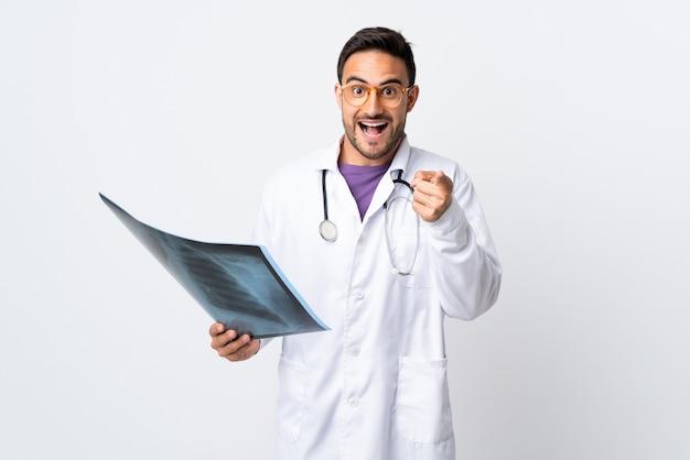 Il giovane medico che tiene una radiografia isolata su fondo bianco punta il dito contro di voi