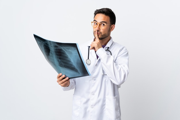 Uomo del giovane medico che tiene una radiografia isolata sulla parete bianca che fa gesto di silenzio