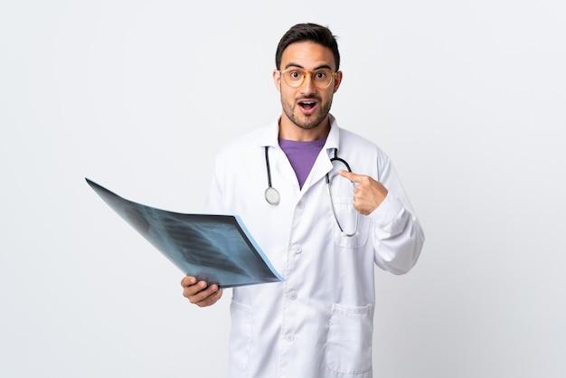 Uomo del giovane medico che tiene una radiografia isolata sulla parete bianca con l'espressione facciale di sorpresa