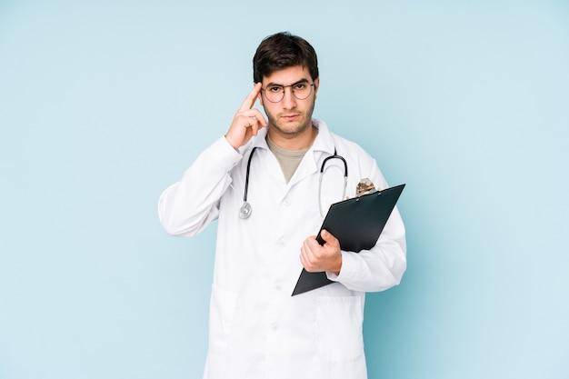 Giovane medico uomo isolato su sfondo blu puntando il tempio con il dito, pensando, concentrato su un compito. Foto Premium