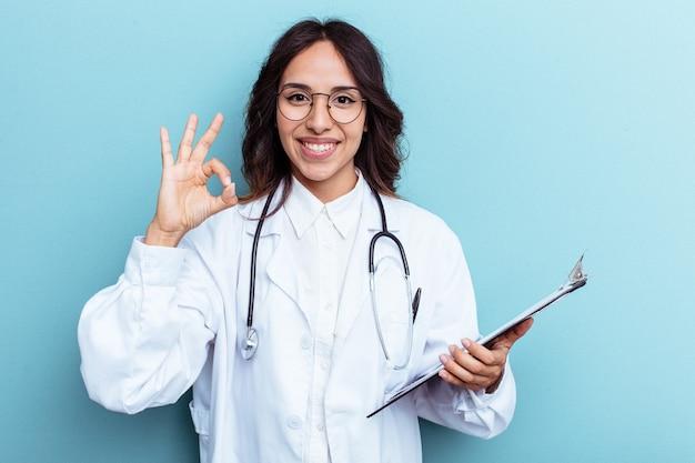 Giovane medico messicano donna isolata su sfondo blu allegro e fiducioso che mostra gesto ok.