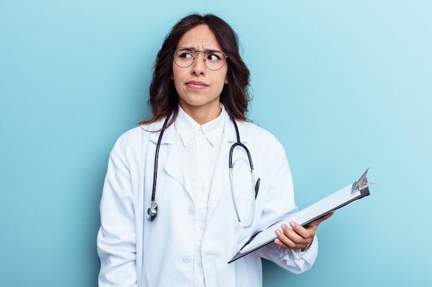 Giovane dottoressa messicana isolata su sfondo blu confusa, si sente dubbiosa e insicura.