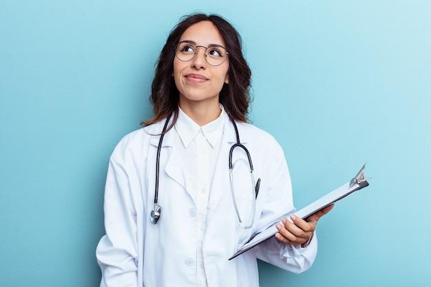 Giovane medico donna messicana isolata su sfondo blu che sogna di raggiungere obiettivi e scopi