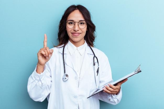 Giovane medico messicano donna isolata su sfondo blu che mostra il numero uno con il dito.