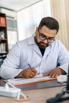 Giovane medico seduto alla scrivania. diagnosi scritta di specialista medico. prescrizione di farmaci.