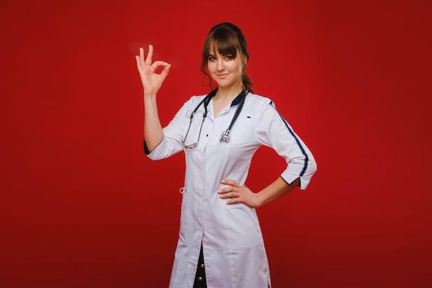 Un giovane dottore sta su un rosso e mostra la sua mano che andrà tutto bene