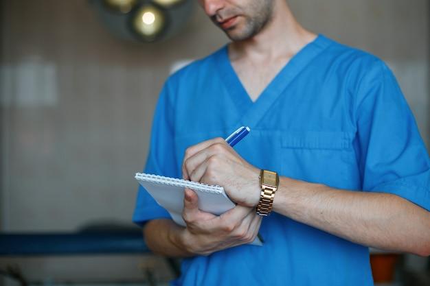 Il giovane chirurgo medico in vestiti medici blu si siede nella sala operatoria e scrive su un taccuino