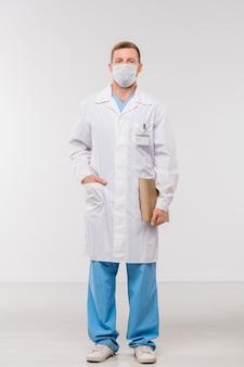 Giovane medico o chirurgo in whitecoat, uniforme e maschera protettiva che tiene documento mentre levandosi in piedi in isolamento